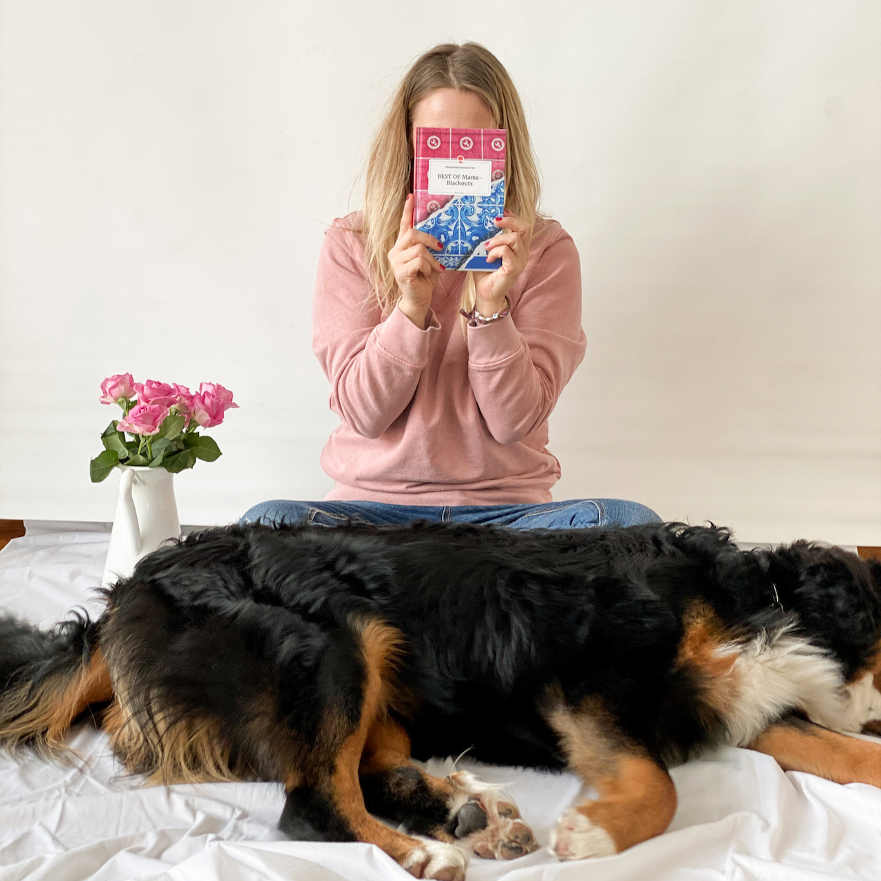 Mama im Homeoffice: Verena arbeitet von daheim aus. Hier haltet sie ihr Buch vor den Kopf und der Hund sitzt vor ihr.